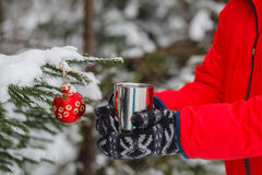 Person is holding a cup of hot drink outdoor. The weather is ver Royalty Free Stock Photo