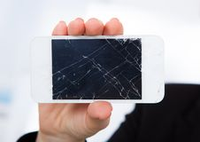 Person holding damaged cellphone. Close-up Of Hand Holding Smartphone With Cracked Screen stock images