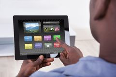 Person holding digital tablet. Close-up Of African Person Holding Digital Tablet Showing Icons Royalty Free Stock Image