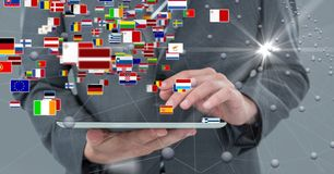 Person holding digital tablet with various flags and connecting dots. Digital composite of Person holding digital tablet with various flags and connecting dots royalty free stock image