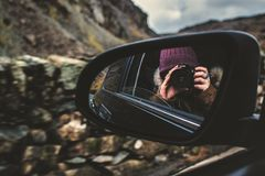 Person Holding Dslr Camera Reflected on Black Framed Wing Mirror Stock Photography