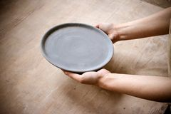 Person holding an empty plate on a wooden table. Top view Royalty Free Stock Photo