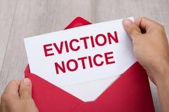 Person Holding Eviction Notice In-Umschlag lizenzfreie stockbilder