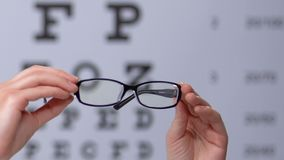 Person holding eyeglasses against eyechart, vision disorder prevention, clinic. Stock footage stock footage