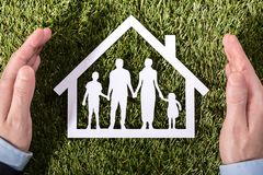 Person Holding Family Home On Grass. High Angle View Of A Person`s Hand Holding Family Home On Green Grass stock image