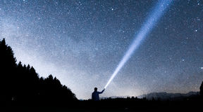 Person Holding Flashlight Towards Sky during Night Stock Image