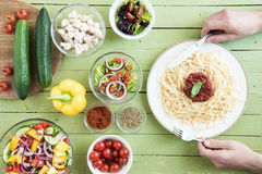 Person holding fork and knife while eating spaghetti with sauce and basil and fresh raw vegetables on wooden table Royalty Free Stock Photo