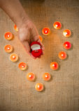 Person holding golden ring in box against heart made of candles. Conceptual photo of person holding golden ring in box against heart made of candles Royalty Free Stock Images