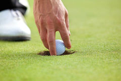 Person holding golf ball, close-up Royalty Free Stock Image