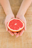 Person holding grapefruit slice at table Royalty Free Stock Images