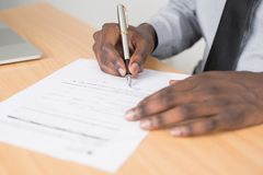 Person Holding Gray Twist Pen and White Printer Paper on Brown Wooden Table royalty free stock photo