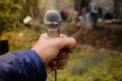 Person Holding Grey Corded Microphone in Selective Focus Photography Photo Taken Stock Images