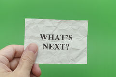 Person holding grey paper note with question What is next. In his hand. Green background Stock Photography