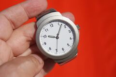 Person Holding Grey Round Analog Watch at 10:07 Royalty Free Stock Images