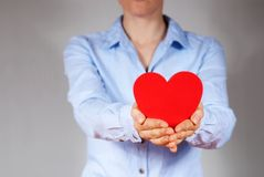 Person holding a heart. A person in blue shirt holding a heart as a gift Stock Photography