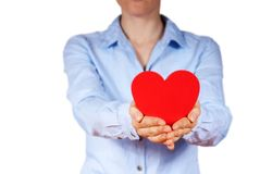 Person holding a heart. A person with blue shirt holding a heart in its hands, isolated Royalty Free Stock Photography
