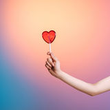 Person holding heart-shaped lollipop in studio. Cropped shot of person holding heart-shaped lollipop in studio Royalty Free Stock Images