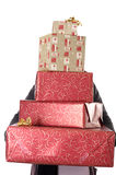 Person holding & hidden behind a stack of presents Royalty Free Stock Photo