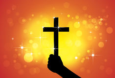 Person holding holy cross,christian religious symbol,in hand. (fist) - concept of a devout faithful christian worshiping Jesus Christ with yellow and orange Stock Image