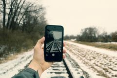 Person Holding Iphone Taking Photo of Train Rails Royalty Free Stock Photography