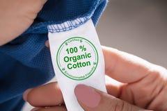 Person Holding Label Showing 100 Percenten Organische Katoenen stock fotografie