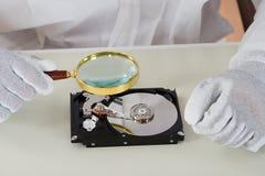 Person Holding Magnifying Glass Over-Festplatte Stockbilder