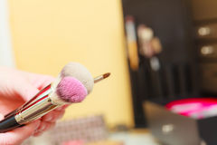 Person holding makeup brushes for blush, powder, lips. Visage concept. Makeup brushes for blush, powder, lips and contour, cosmetics in background Royalty Free Stock Image