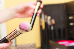 Person holding makeup brushes for blush and powder. Visage concept. Makeup brushes for blush, powder and contour, cosmetics in background Stock Images