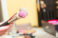 Person holding makeup brushes for blush and powder. Visage concept. Makeup brushes for blush, powder and contour, cosmetics in background Stock Photography