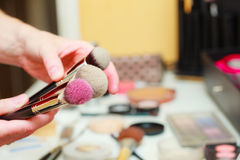 Person holding makeup brushes for blush and powder Royalty Free Stock Photos