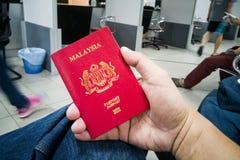 Person holding Malaysia international passport Stock Images