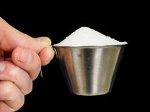 Person holding a measuring cup of sugar. Person holding a measuring cup of one deciliter filled up with white granulated sugar, isolated on black Royalty Free Stock Photography