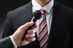 Person holding microphone in front of businessman Stock Photo