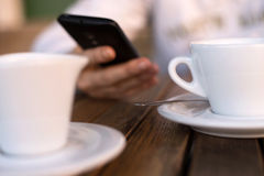 Person holding mobile phone while drinking coffee Royalty Free Stock Photo
