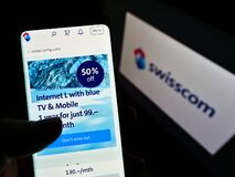 Person holding mobile phone with logo of Swiss telecommunications company Swisscom on screen in front of website.