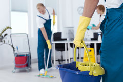 Person holding a mop pail. Image of person holding mop pail and men cleaning floor Royalty Free Stock Images