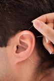Person holding needle near ear Stock Photo