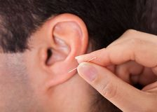 Person holding needle near ear Stock Images