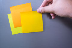 Person holding note sticked on fridge door Royalty Free Stock Images