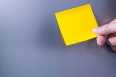 Person holding note sticked on fridge door Stock Photo