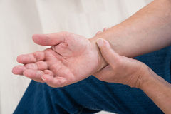 Person Holding Painful Wrist arkivfoto