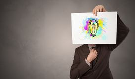 Person holding a paper with colorful bulb concept. Person holding a paper with a drawn colorful idea concept royalty free stock photos