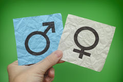Person holding paper notes with Gender Symbols in his hand. Green background stock images