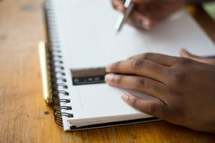 Person Holding a Pen Writing on White Notebook Stock Photo