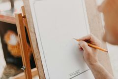 Person Holding Pencil on White Canvas Royalty Free Stock Images