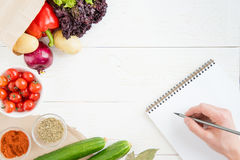 Person holding pencil and writing recipe in cookbook while cooking Stock Image