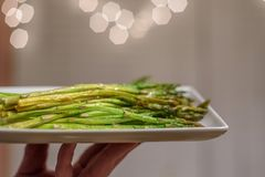 Person holding a plate of fresh steamed asparagus in restaurant royalty free stock photography