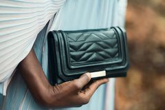 Person Holding Quilted Black Leather Clutch Bag stock image