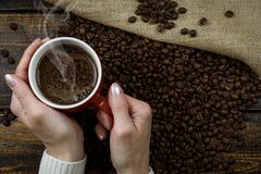 Person Holding Red Cup of Coffee Cup With Coffee Above Coffee Beans Stock Photo
