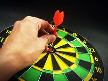 Person Holding Red Dart on Green Yellow and Black Dart Board Royalty Free Stock Photo